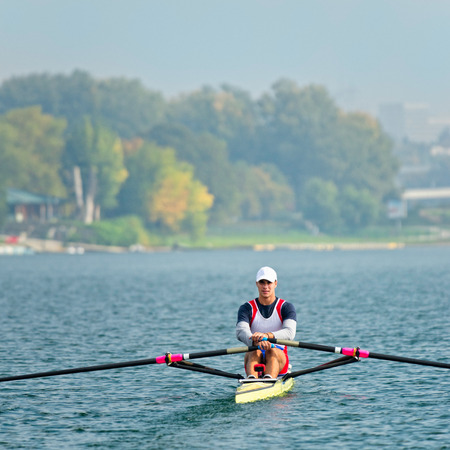 sculling: Front view of young athlete rowing on a lake Stock Photo