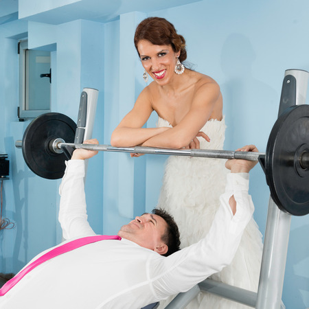 gym dress: Smiling bride adding weight to a hardworking groom Stock Photo