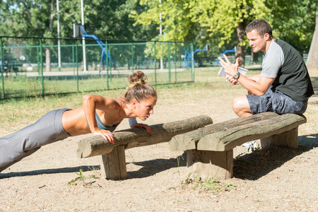 two people only: Personal fitnes trainer counting push ups Stock Photo