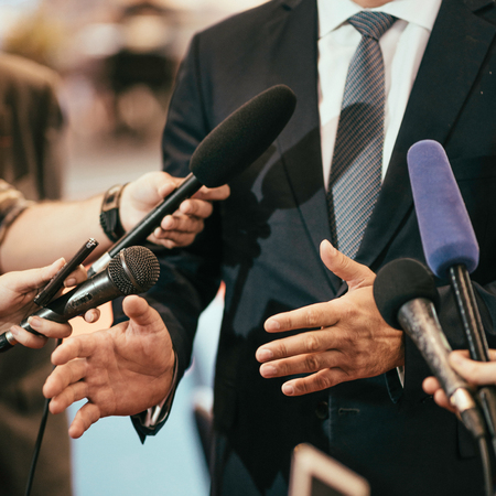 spokesperson: Media microphones surrounding politician or business person Stock Photo