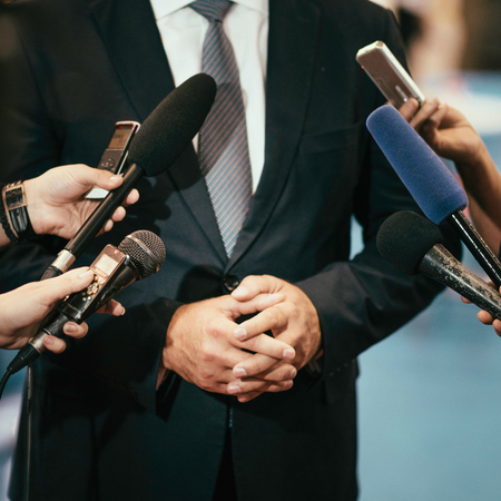 answering: Politician or business persons answering to media journalists Stock Photo