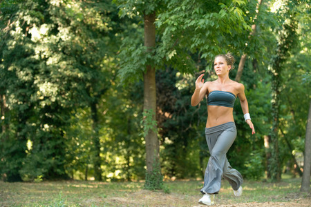 conscious: Attractive body conscious young women jogging in park