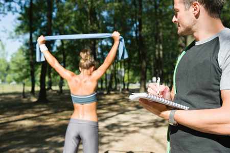 resistance: Personal fitness trainer with client, resistance band exercise, focus on hand and notebook