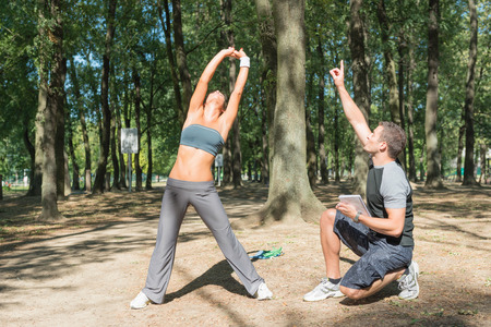 only two people: Personal fitness instructor supervising young woman during body rotation exercise