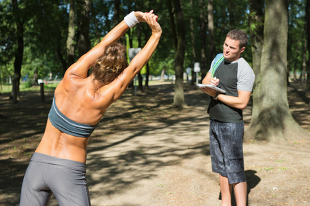 Young woman stretching with sports instructor in urban park