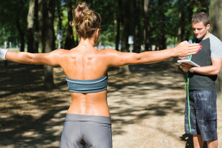 only mid adult men: Young woman with arms outstretched, exercising with personal trainer