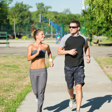 recreational area: Two young adults jogging in urban recreational area Stock Photo