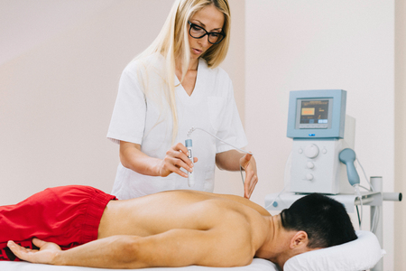 laser beam: Therapeutic laser technology - Physical therapist pointing medical laser beam to a spot on a patients back