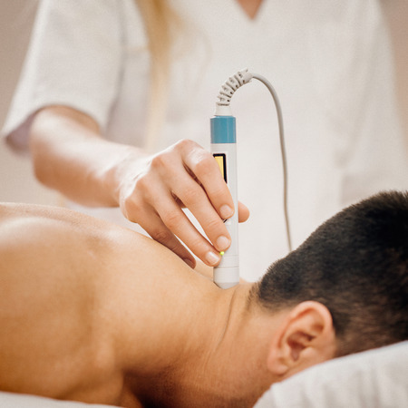 Therapeutic laser technology - therapist pointing medical laser beam to a spot on a patient's neck Stock Photo