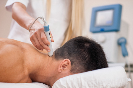laser beam: Therapeutic laser technology - therapist pointing medical laser beam to a spot on a patients neck