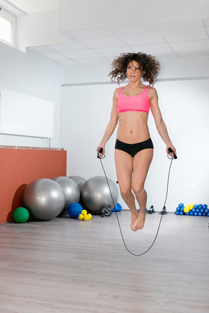 vertical wellness: Attractive girl jumping rope in a gym Stock Photo