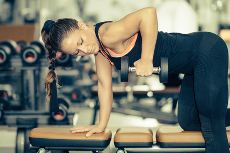 toned image: Attractive female athlete exercising in modern gym. Toned image