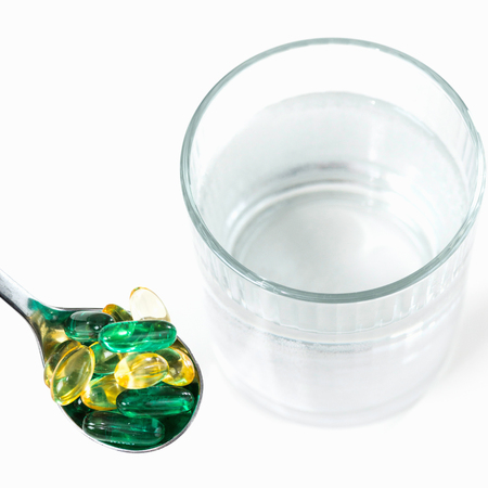 nutritional therapy: Vitamin pills with glass of water. White background, high key