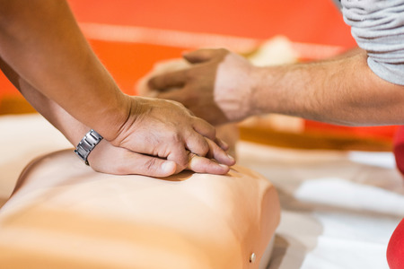 paramedics: CPR chest compressions - paramedics practicing with CPR dummy