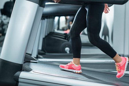 only one person: Woman using incline threadmill in modern gym. Incline threadmills are used to simulate uphill walking or running and deliver additional workout benefits to users. Woman is wearing black yoga pants andrunning sports shoes. Stock Photo