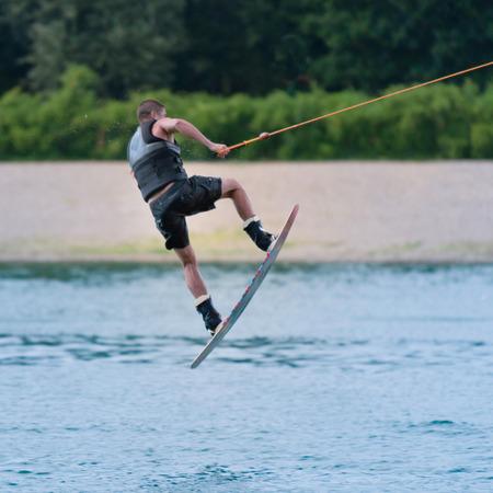waterskiing: Wakeboarder performing stunt