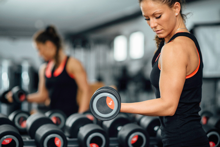 toned image: Attractive female athlete exercising in modern gym. Toned image, focus on dumbbell