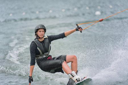 waterskiing: Cool girl wakeboarding, looking to camera Stock Photo