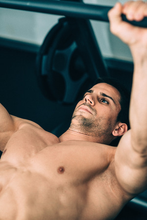 only one mid adult male: Muscular man lifting weights, lying on weight bench gym. Focus on face, color graded image