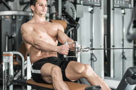 only one mid adult male: Muscular young man exercising on rowing machine in modern gym.