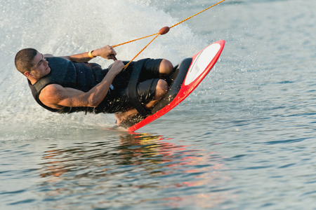 exhilaration: Young man doing a kneeboarding stunt at high speed