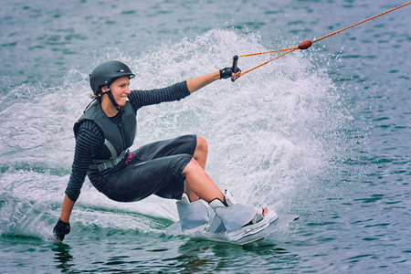 wet suit: Woman touching the water with one hand and holding a rope with the other hand while wake boarding on dark-blue water. She is wearing a black helmet and black wet suit. Stock Photo