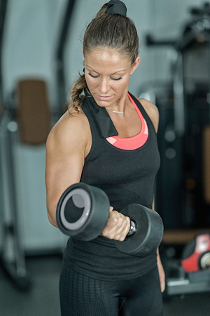 only the biceps: Woman in health club exercising with weights
