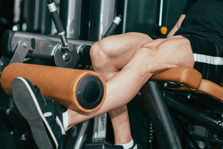 only one mid adult male: Muscular man exercising in gym, leg extension machine exercising