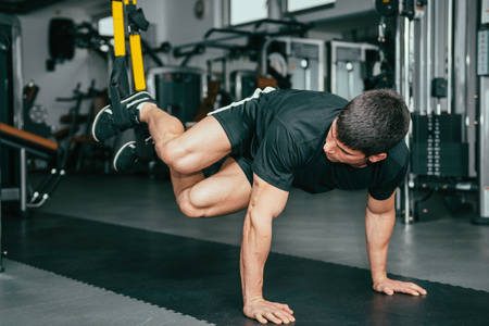 Muscular man exercising in health club. Using TRX bands, doing push-ups and torso rotations with legs suspended.