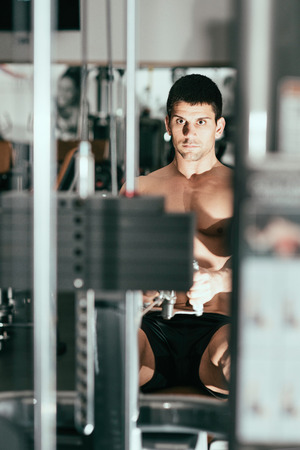 one mid adult man only: Muscular young man exercising on rowing machine in modern gym. Focus set on face, exercising machine and gym blurred. Toned image