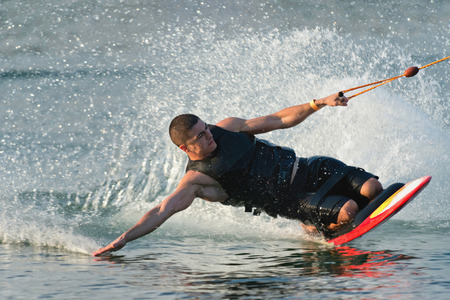 waterskiing: Young man kneeboading, touching water surface at high speed Stock Photo