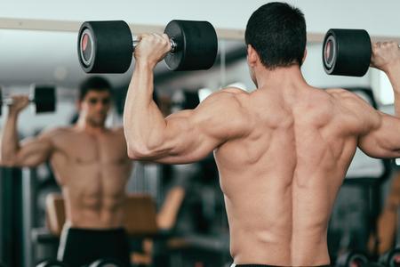 campione del body building esercizio in palestra, in piedi davanti allo specchio