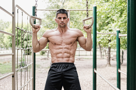 muscular build: Muscular build male model exercising on gymnastic rings in outdoor gym
