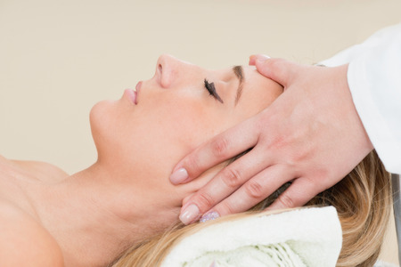 Young woman enjoying head massage in massage center Archivio Fotografico