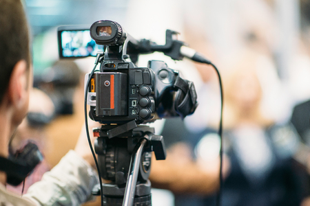 commercial event: Television camera recording publicity event. Camera in focus, operator and event blurred Stock Photo