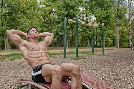 situp: Muscular young man doing crunches on sit-up board in park