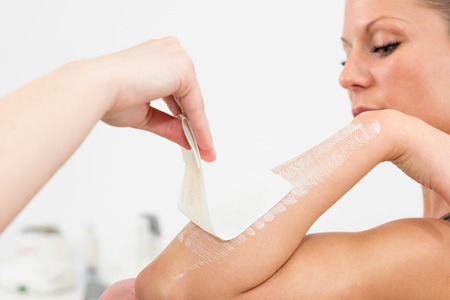 only two people: Waxing ladys forearm in beauty salon