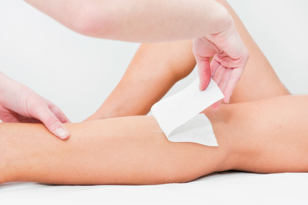 vax: Leg waxing - beautician removing hair from legs at beauty center