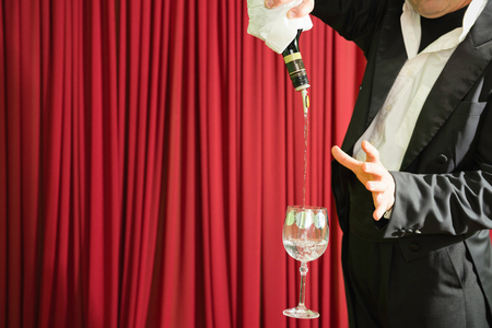 magic trick: Magic trick with bottle and glass, stage performance Stock Photo