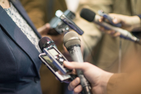 spokesperson: Group of journalists interviewing politician, holding microphones and voice recorders Stock Photo