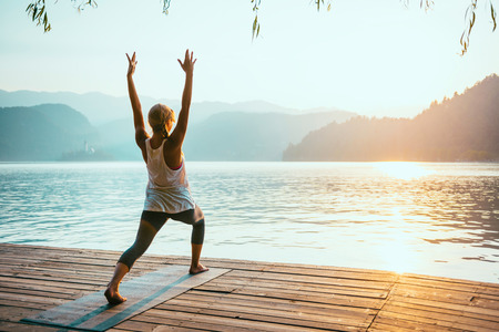 Beautiful woman practicing Yoga by the lake - Sun salutation series - Virabhadrasana - Toned image