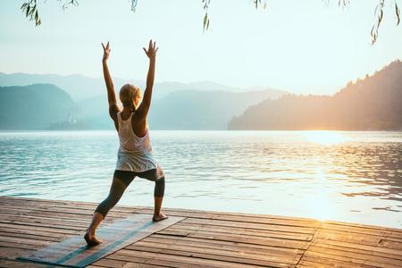 buena postura: Hermosa mujer practicando yoga en el lago - Serie saludo al sol - Virabhadrasana - Imagen entonada