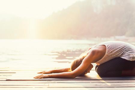 Krásná žena cvičí jógu u jezera - Sun oslovení series - Balasana nebo postavení dítěte - tónovaný obraz