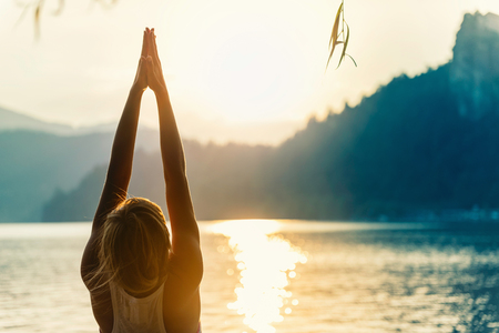 Beautiful woman practicing Yoga by the lake - Sun salutation series - Upward hands pose - Toned image Banco de Imagens - 57149886