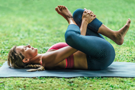 reclining: Young woman doing Yoga, reclining position Stock Photo