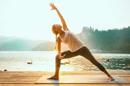 Beautiful woman practicing Yoga by the lake - Sun salutation series - Extended triangle pose - Water birds - Toned image