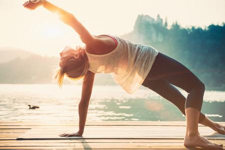 美しい女性が湖のほとりでヨガの練習します。日没。トーンのイメージ