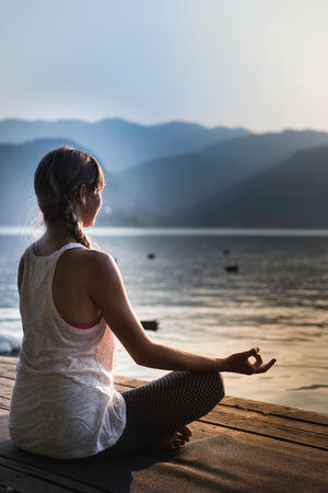 water birds: Young woman meditating by the lake, sunset, water birds