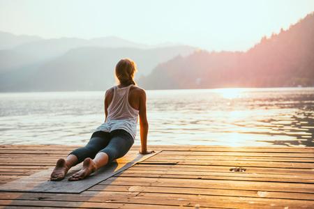 buena postura: Hermosa mujer practicando yoga en el lago - Serie saludo al sol - perro mirando hacia arriba - Imagen entonada