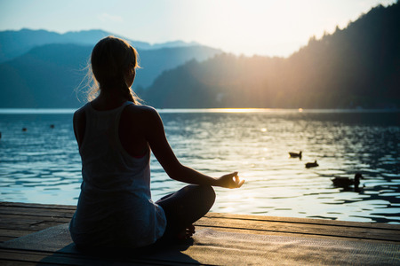 Young woman meditating by the lake, sunset, water birds